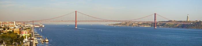 Panorama van brug 25 DE Abril op rivier Tagus bij zonsondergang, Lissabon, Stock Foto's