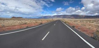 Panorama van de lege weg door zandige en vulkanische woestijn Stock Afbeelding