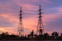 Panorama van de lijnen van de hoogspanningsmacht dichtbij water bij zonsondergang Royalty-vrije Stock Foto