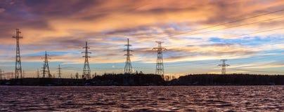 Panorama van de lijnen van de hoogspanningsmacht dichtbij water bij zonsondergang Royalty-vrije Stock Afbeelding