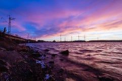 Panorama van de lijnen van de hoogspanningsmacht dichtbij water bij zonsondergang Royalty-vrije Stock Afbeeldingen
