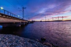 Panorama van de lijnen van de hoogspanningsmacht dichtbij water bij zonsondergang Stock Afbeelding