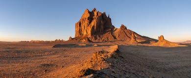 Panorama van de Shiprock-rotsvorming die boven een enorm landschap in dramatisch vroeg ochtendlicht toenemen stock foto