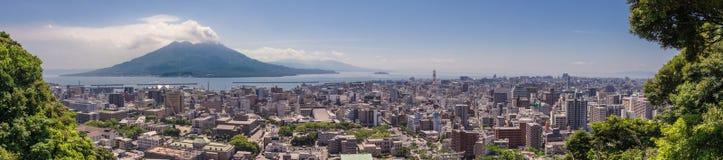 Panorama van de Stad van Kagoshima met losgebarsten Vulcan Sakurajima en de Baai van Kagoshima op een duidelijke de zomerdag Geve stock foto