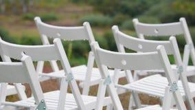 Panorama van de verscheidenheid van wit die stoelen op het gebied van huwelijksregistratie vouwen bij de huwelijksceremonie met d stock footage
