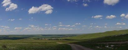Panorama van de weg onder de blauwe hemel met wolken Royalty-vrije Stock Afbeeldingen