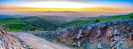 Panorama van de zonsondergang in een groene vallei stock fotografie