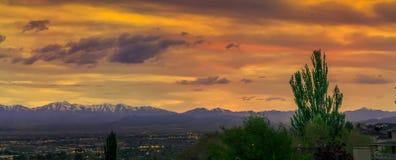 Panorama van een vallei met de stadslichten en bergen op de achtergrond onder een overweldigende zonsondergang stock fotografie