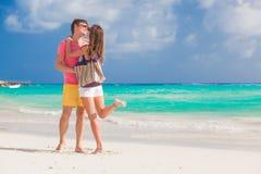 Panorama van gelukkig jong paar die in zonnebril in heldere kleren op tropisch strand flirten Stock Afbeeldingen