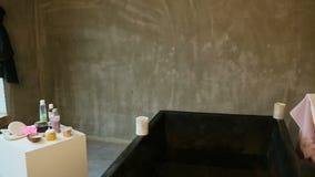 Panorama van grote badkamers met groot diep zwart bad met warm water stock video