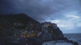Panorama van het dorp en de golven die van avondmanarola over rotsen verpletteren stock video