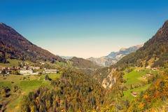 Panorama van het dorp van Vättis en brug tegen de achtergrond van de Zwitserse Alpen bij zonsondergang St Gallen, Zwitserland stock fotografie