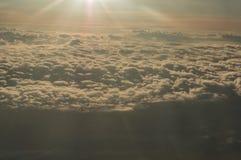 Panorama van het venster van het vliegtuig die boven de zonovergoten wolken vliegen stock foto's