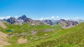 Panorama van hierboven op de pieken van de hoge hoogteberg, groene weiden en blauw meer in idyllisch niet besmet milieu eens cove stock video