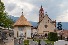 Panorama van hoofdkerk, Pfarrkirche St Johannes der Taufer, met Kerkhof en Kapel in het gemeentedorp van Tirol stock fotografie