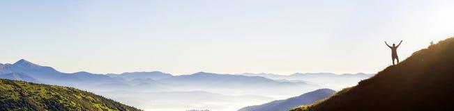Panorama van jonge succesvolle het silhouet open wapens van de mensenwandelaar op bergpiek royalty-vrije stock foto's