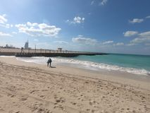 Panorama van Jumeirah-Strand en Burj Al Arab en Weergeven van Pijler Vrouw die Shells opnemen bij strand royalty-vrije stock foto's