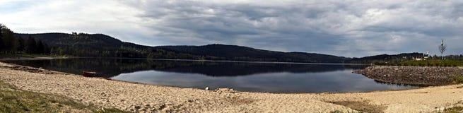 Panorama van Lipno-waterreservoir met kano, zandige strand en heuvels stock afbeelding