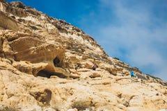 Panorama van Matala-strand De holen op de rotsen werden gebruikt als roman begraafplaats en bij het decennium Stock Foto's