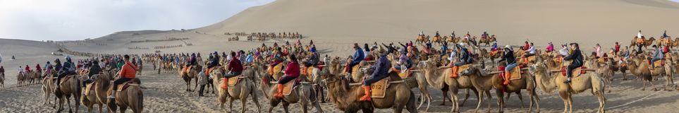 Panorama van menigten bij kameelritten, Zingende Zandberg, Taklam stock afbeelding