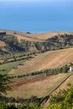 Panorama van olijfgaarden en landbouwbedrijven op rollende heuvels van Abruzzo en op de achtergrond het Adriatische Overzees stock afbeelding