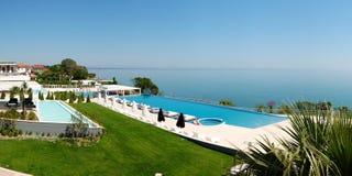 Panorama van oneindigheids zwembad door strand Stock Afbeeldingen