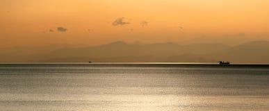 Panorama van schip bij zonsondergang met bergen stock afbeeldingen