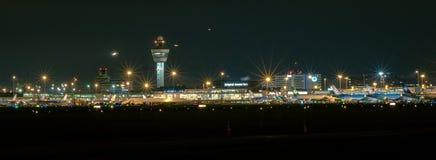 Panorama van Schiphol Amsterdam Internationale 's nachts Luchthaven stock afbeelding