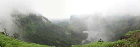 Panorama van wolken die over bergen hangen die vijver overzien stock foto