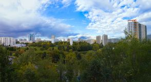 """Panorama van woondisctrict van Moskou met mooie wolken in blauwe hemel†""""sovjethuizen en groot park stock foto"""