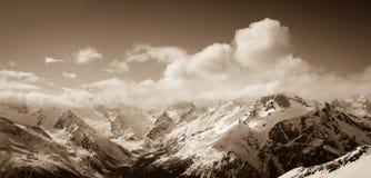 Panorama van zonnige de winterbergen in wolken Stock Afbeeldingen