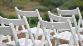 Panorama of the variety of white folding chairs in the area of marriage registration at the wedding ceremony with drops. From the rain. Wet seat in the open air stock footage