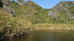 Panorama view of beautiful karst scenery, wetlands. Seen from the boat at Van Long Nature Reserve, Vietnam. Tourists traveling in small boat in tranquil stock video footage