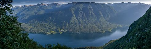 Panorama view of the blue lake Bohinjsko jezero. Panorama view of the blue lake Bohinjsko jezero surrounded with green grass and trees. Summer in Julian Alps Royalty Free Stock Image