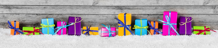 Panorama View of Colored Gift Boxes on Snow. Panorama View of Beautiful Colored Gift Box Decorations on the Snow with Vintage Wooden Wall Behind royalty free stock images