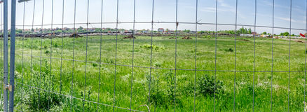 Panorama view on the construction site through a fence wire stock images