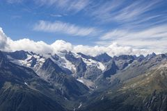 Panorama view of dramatic sky and mountains scene in national park Dombay. Panorama view of dramatic blue sky and mountains scene in national park Dombay stock photography