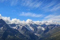 Panorama view of dramatic sky and mountains scene in national park Dombay. Panorama view of dramatic blue sky and mountains scene in national park Dombay royalty free stock photos