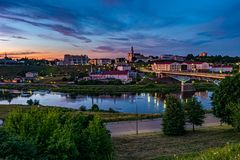 Panorama view on evening in old town on the bank of wide river with evening fluffy curly rolling cirrostratus clouds and blue stock photo