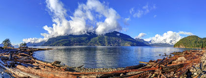 Panorama view from Furry Creek, BC, Canada, with dramatic cloudscape and driftwood on beach in winter time stock photos