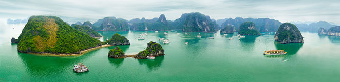 Panorama view of Ha Long Bay, Vietnam. Tourist junks floating among limestone rocks at early morning in Ha Long Bay, South China Sea, Vietnam, Southeast Asia