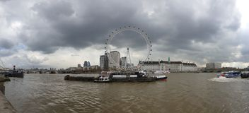 Panorama view of the London Eye over looking ominous storm clouds, London, Westminster. Panorama view london eye over looking ominous storm clouds westminster royalty free stock photography