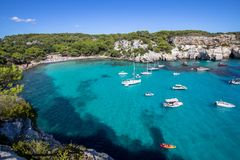 Boats and yachts on Macarella beach, Menorca, Spain. Panorama view of Macarella beach in Menorca, Balearic Islands, Spain Royalty Free Stock Images