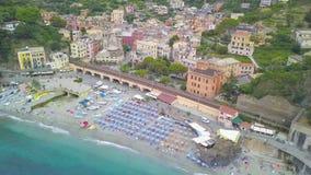 Panorama view of Monterosso al Mare village one of Cinque Terre in La Spezia, Italy. Flight along the beach, umbrellas, people