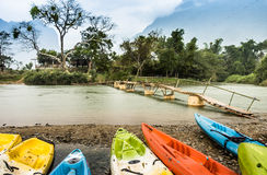 Kayaking on Nam Song river in Vang Vieng, Laos - Rainy Day. Panorama view of Nam Song River in Vang Vieng with some colored kayaks ready to be used Royalty Free Stock Images