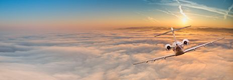 Private jet plane flying above dramatic clouds. Panorama view of private jet plane flying above dramatic clouds during sunset stock photo