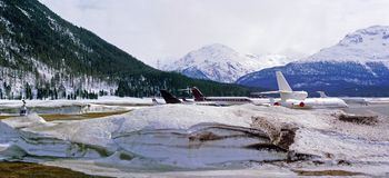 A panorama view of private jets, planes and helicopters in the snowy airport in the alps switzerland in winter Royalty Free Stock Images