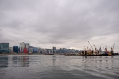 Panorama view of river, business district and crane boat on cloudy sky background stock image