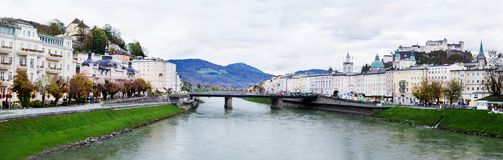 Panorama view of Salzach river in Salzburg, Austria. Autumn city landscape with both banks river and buildings. Bridge over river Salzach, mountains Alps on Royalty Free Stock Photo