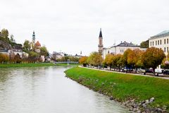 Panorama view of Salzach river in Salzburg, Austria. Autumn city landscape with river and buildings, green grass and yellow trees Royalty Free Stock Image